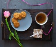 Sira de mãe ao dia do ` s, dia do ` s da mulher tulipas, presentes, chá e doces no fundo de madeira Foto de Stock