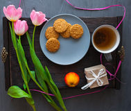 Sira de mãe ao dia do ` s, dia do ` s da mulher tulipas, presentes, chá e doces no fundo de madeira Foto de Stock Royalty Free