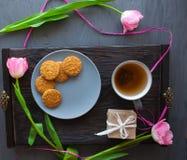 Sira de mãe ao dia do ` s, dia do ` s da mulher tulipas, presentes, chá e doces no fundo de madeira Fotografia de Stock Royalty Free