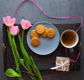 Sira de mãe ao dia do ` s, dia do ` s da mulher tulipas, presentes, chá e doces no fundo de madeira Fotos de Stock
