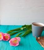 Sira de mãe ao dia do ` s, dia do ` s da mulher tulipas, presentes, chá e doces no fundo de madeira Imagem de Stock
