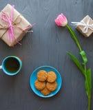 Sira de mãe ao dia do ` s, dia do ` s da mulher tulipas, presentes, chá e doces no fundo de madeira Imagens de Stock