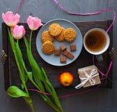 Sira de mãe ao dia do ` s, dia do ` s da mulher tulipas, presentes, chá e doces no fundo de madeira Fotografia de Stock