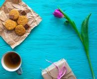 Sira de mãe ao dia do ` s, dia do ` s da mulher tulipas, presentes e doces no fundo de madeira Imagem de Stock