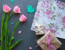 Sira de mãe ao dia do ` s, dia do ` s da mulher tulipas, presentes e letra no fundo de madeira Foto de Stock