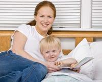 Sira de mãe ao filho da leitura uma história de horas de dormir na cama Fotos de Stock