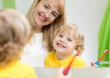 Sira de mãe ao filho de ensino da criança para escovar seus dentes na frente do espelho do banheiro foto de stock royalty free