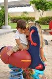 Sira de mãe ao jogo com seu filho pequeno no campo de jogos Foto de Stock Royalty Free