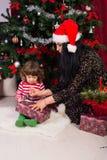 Sira de mãe ao menino da criança da ajuda para abrir o presente do xmas Imagem de Stock
