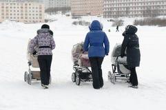 Sira de mãe ao passeio com um carrinho de criança no inverno Foto de Stock