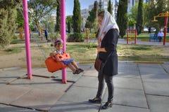Sira de mãe ao rapaz pequeno de balanço no balanço no parque, Shiraz, Irã Imagem de Stock