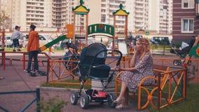 Sira de mãe ao transporte de bebê do balanço no campo de jogos das crianças e fale no telefone Miúdos filme
