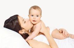 Sira de mãe a beijar o bebê e ao encontrar-se na cama foto de stock