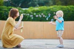 Sira de mãe a bolhas de sopro e ao jogo com seu filho pequeno Imagem de Stock Royalty Free
