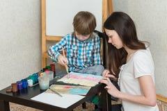 Sira de mãe com cores da pintura do filho dos meninos em casa imagem de stock