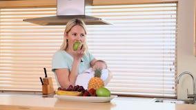 Sira de mãe a comer uma maçã ao guardar seu bebê vídeos de arquivo