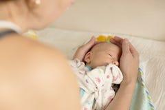 Sira de mãe a consolá-la um bebê recém-nascido após ter mudado tecidos fotos de stock