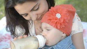 Sira de mãe a dar mamadeira seu bebê recém-nascido no parque filme