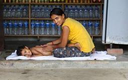 Sira de mãe a dar a massagem da filha em chitwan, Nepal Imagem de Stock
