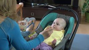 Sira de mãe a dar o alimento a sua criança adorável em casa 4K filme