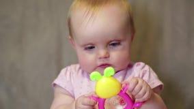 Sira de mãe a dar um brinquedo a uma criança pequena e à criança felizes filme