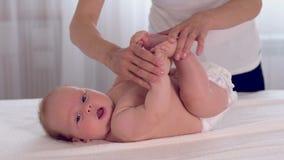 Sira de mãe a dar uma massagem para seu bebê pequeno vídeos de arquivo