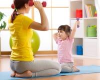 Sira de mãe e caçoe ao treinamento da filha com pesos na sala home foto de stock