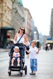 Sira de mãe e dois miúdos que andam no centro de cidade fotografia de stock