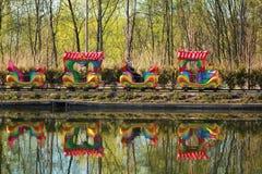 Sira de mãe e duas crianças que montam um parque colorido do trem do carrossel na primavera, reflexão em um lago Fotografia de Stock Royalty Free
