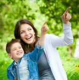 Sira de mãe e seu filho com o livro que senta-se na grama verde fotos de stock