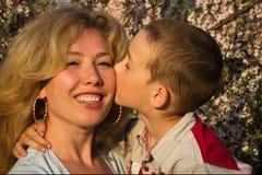 Sira de mãe e seu filho pequeno em um jardim da mola fotos de stock