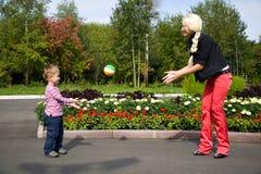 Sira de mãe e seu filho que joga com esfera Fotografia de Stock
