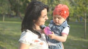 Sira de mãe e seu jogo da menina no parque e olhe à câmera filme