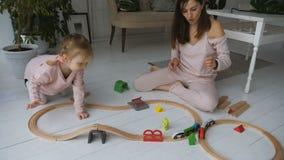 Sira de mãe e seu jogo pequeno da filha com estrada de ferro de madeira vídeos de arquivo