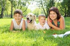 Sira de mãe e seus dois filhos no parque com um cão Fotografia de Stock Royalty Free
