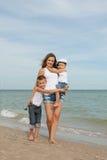 Sira de mãe e seus dois filhos que têm o divertimento na praia Foto de Stock