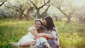 Sira de mãe e seus filha e filho pequenos em um jardim de florescência video estoque