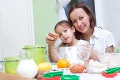 Sira de mãe e sua filha, bakeing na cozinha Fotografia de Stock