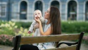 Sira de mãe e sua filha do bebê que joga com bolhas de sopro no jardim vídeos de arquivo