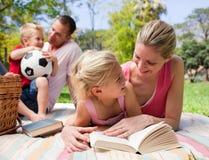 Sira de mãe e sua leitura da filha em um piquenique foto de stock