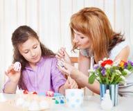 Sira de mãe e sua pintura pequena da filha em ovos da páscoa Imagens de Stock