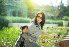 Sira de mãe e uma bicicleta de ciclagem da filha no parque Imagens de Stock