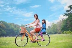 Sira de mãe e uma bicicleta de ciclagem da filha no parque Foto de Stock
