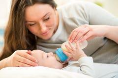 Sira de mãe em casa ao bebê de alimentação com uma garrafa de leite Fotos de Stock Royalty Free
