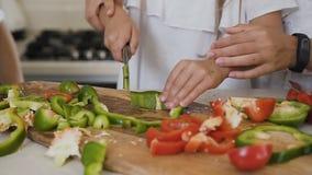 Sira de mãe a ensinar-lhe vegetais do corte da filha em casa na cozinha As meninas cortam pimentas vermelhas e verdes para fazer  filme