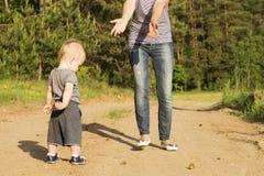 Sira de mãe a ensinar seu filho do bebê de um ano para andar Recue a criança que tenta fazer primeiras etapas imagem de stock royalty free