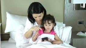 Sira de mãe a ensinar sua filha pequena jogar no móbil vídeos de arquivo