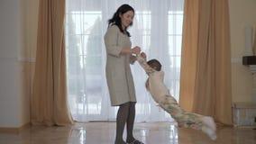Sira de mãe a girar sua filha pequena em torno dsi mesma em casa video estoque