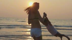 Sira de mãe a girar sua filha pequena no Sandy Beach na luz morna do por do sol video estoque
