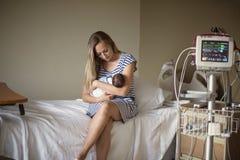Sira de mãe a guardar seu bebê prematuro recém-nascido no hospital imagem de stock